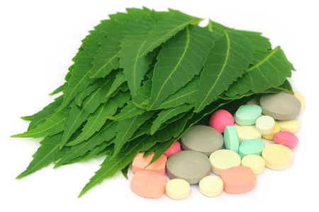 Pills made from medicinal neem leaves over white background photo