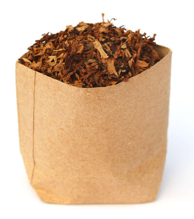 Dried tobacco leaves in  brown paper packet photo