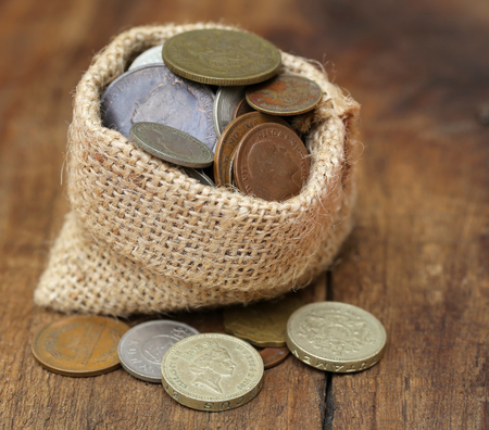 sac: Old coins in sack bag on wooden surface