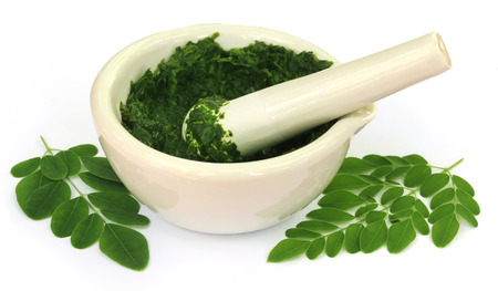 Moringa leaves with mortar and pestle over white background Stockfoto