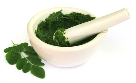 sonjna: Moringa leaves with mortar and pestle over white background Stock Photo