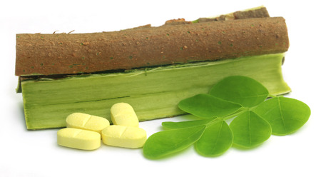 sonjna: Moringa leaves and bark with pills over white background