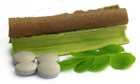 Moringa leaves and bark with pills over white background