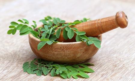 Moringa leaves with mortar and pestle