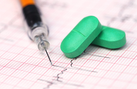 electrocardiograph: Close up of electrocardiograph with pills and syringe