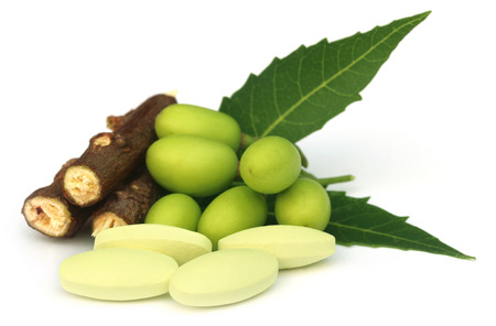 Medicinal neem fruits with tablets over white background photo