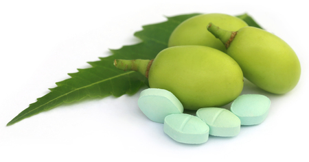 neem: Medicinal neem fruits with tablets over white background Stock Photo