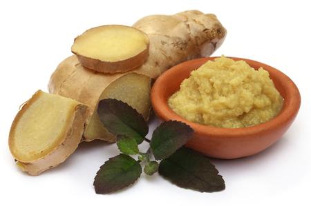 Fresh crushed ginger with holy basil over white background photo