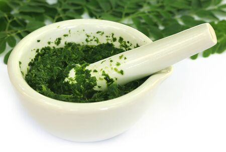 kelor: Moringa leaves with mortar and pestle over white background Stock Photo