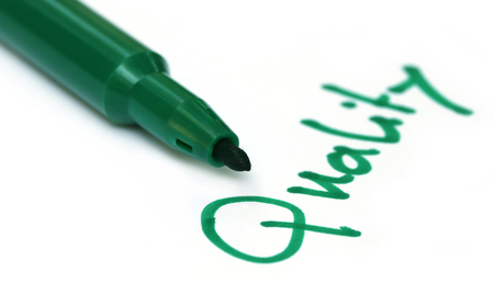 pen quality: Quality written on a white paper with green pen Stock Photo