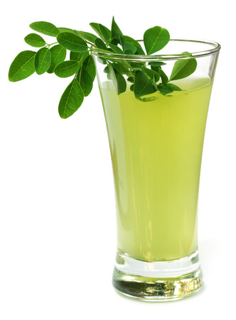 ben oil: Ayurvedic Juice made from moringa leaves over white background