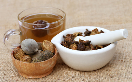Tea made from Triphala, a combination of ayurvedic fruits with mortar and pestle Archivio Fotografico