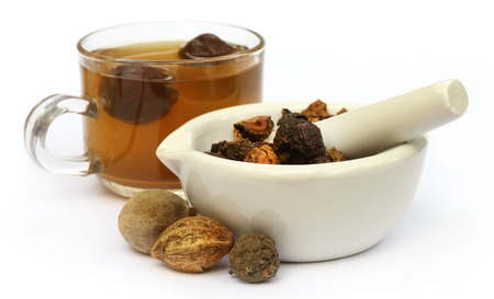 Triphala、乳鉢と乳棒でアーユルヴェーダ果実の組み合わせから作られた茶