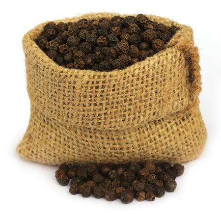 black pepper: Black peppercorns in sack over white background