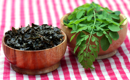 saijhan: Fried and green moringa leaves in wooden bowls Stock Photo