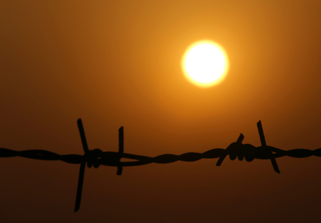 Setting sun behind a fence of barbed wire photo