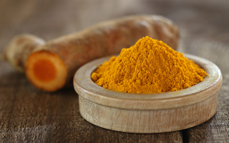 curcumin: Raw and ground turmeric on wooden surface Stock Photo