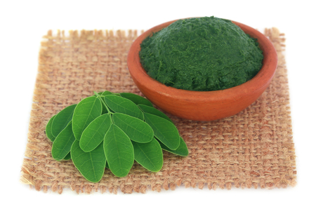 marango: Edible moringa leaves with ground paste on sack surface Stock Photo