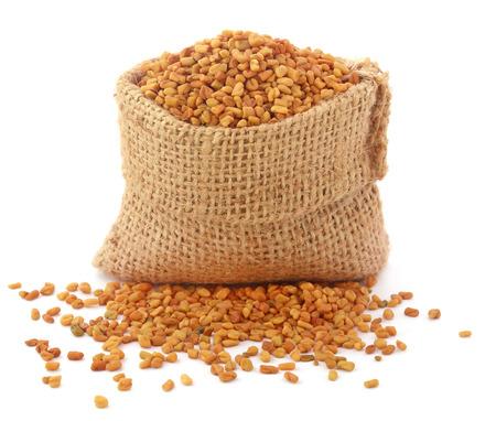 fenugreek: Fenugreek seeds in sack over white background Stock Photo