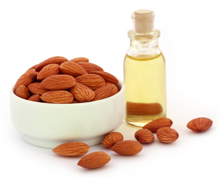essential oil: Fresh almonds with bottle of oil over white background