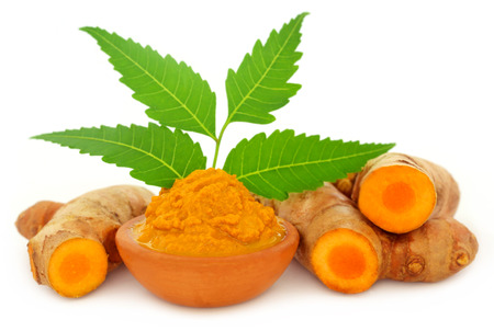 Medicinal turmeric paste with neem leaves over white background Standard-Bild