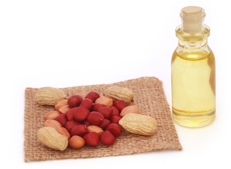 cooking oil: Fresh Peanuts with cooking oil over white background