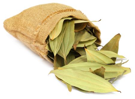 cinnamomum: Cassia leaves in sack over white background