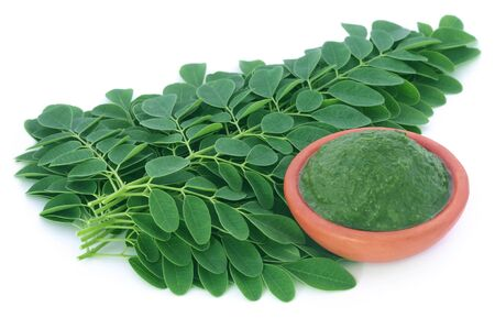 sajna: Moringa leaves with mashed ones in a bowl over white background