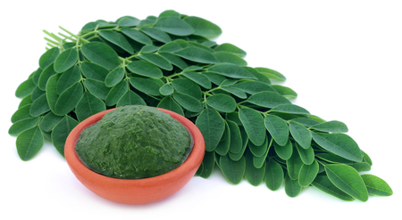 Moringa leaves with mashed ones in a bowl over white background
