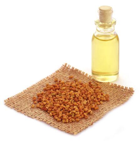 fenugreek: Fenugreek with oil in bottle over white background