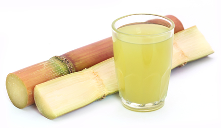 sugarcane: Pieces of sugarcane juice in a glass over white background