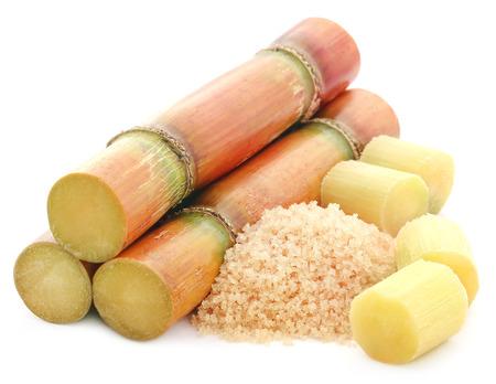 白い背景上赤糖とサトウキビの作品