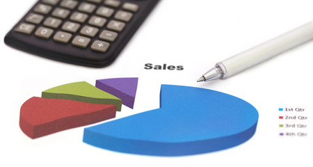 sales chart: Sales chart with a silver ballpoint and calculator over white background Stock Photo