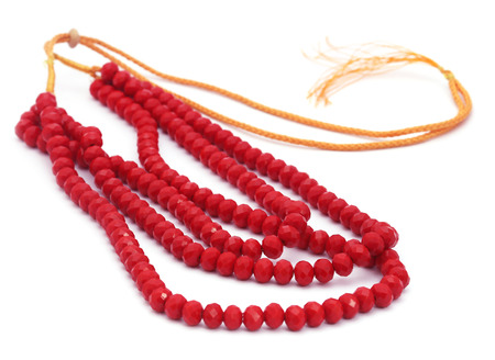 indian money: Red bead necklace over white background