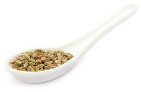 fennel seeds: Fennel seeds in spoon over white background Stock Photo