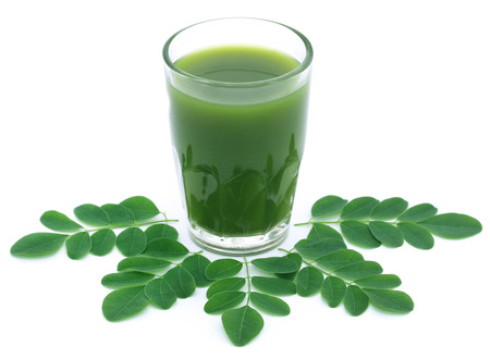 Moringa leaves with extract in a glass over white background Standard-Bild