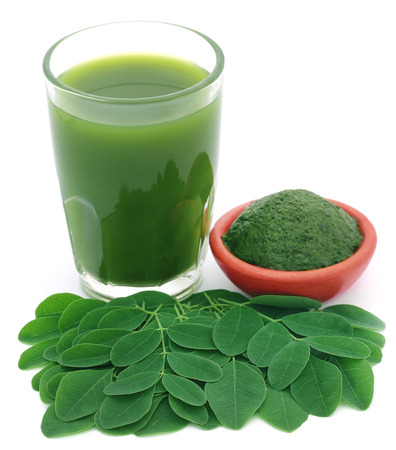 malunggay: Moringa leaves with extract in a glass over white background Stock Photo