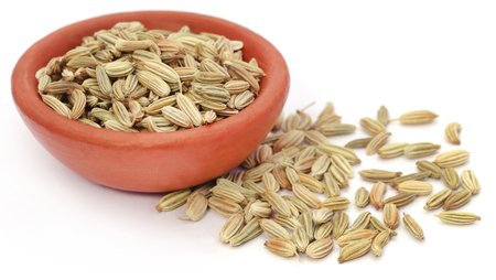 fennel seeds: Fennel seeds in a  pottery over white background