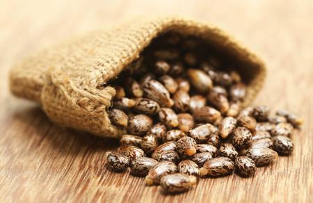 sacco juta: semi di ricino nel sacco di iuta sulla superficie di legno