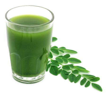 marango: Moringa leaves with juice in a glass over white background