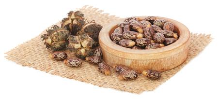 sacco juta: semi di ricino in una ciotola sul sacco di iuta su sfondo bianco