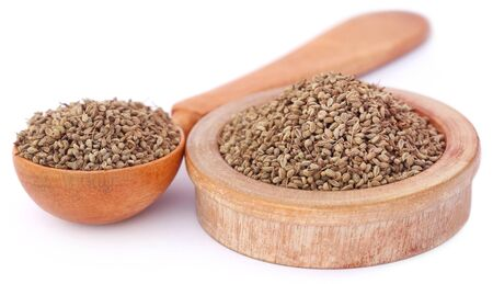 ajwain: Ajwain seeds in a wooden bowl and spoon over white background Stock Photo