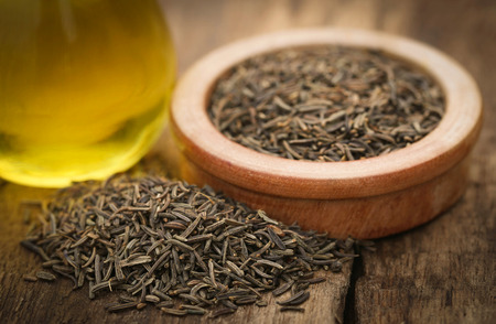 caraway: Caraway seeds with essential oil on wooden surface