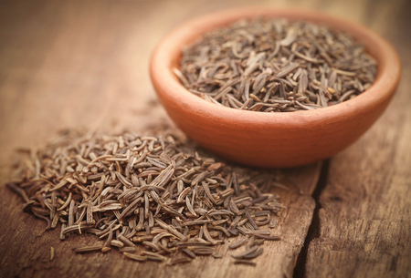 caraway: Caraway seeds in a pottery on wooden surface