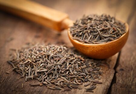 Caraway seeds in a spoon on wooden surface Stock Photo