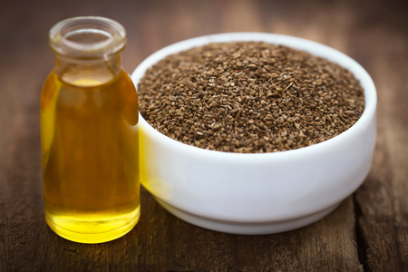 ajwain: Ajwain seeds in a bowl with essential oil on wooden surface