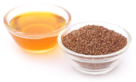 ajwain: Ajwain seeds in a glass bowl with essential oil over white background