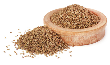ajwain: Ajwain seeds in a wooden bowl over white background Stock Photo