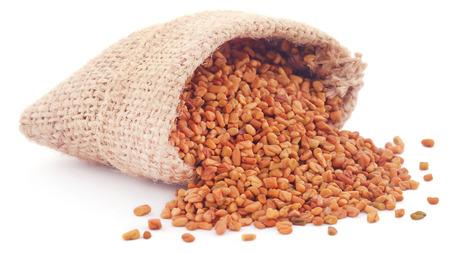 methi: Fenugreek seeds in sack over white background Stock Photo