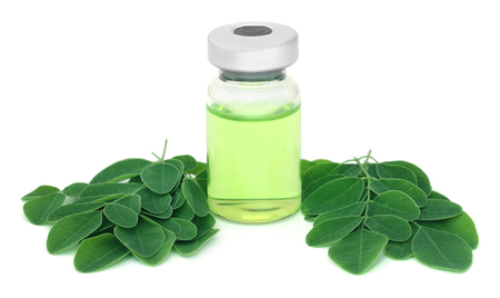 malunggay: Moringa leaves with medicine in vial over white background Stock Photo